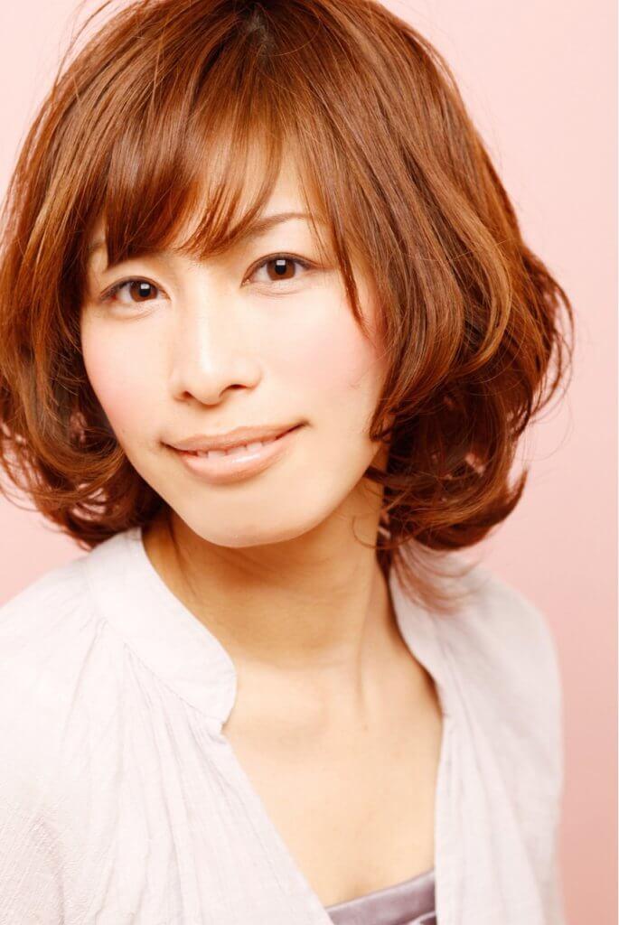 オレンジ系の色味の短いパーマスタイルの笑顔の女性の写真
