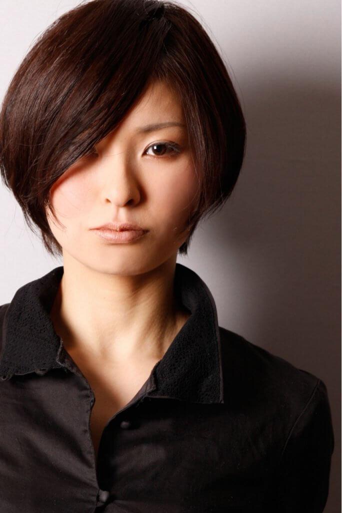 正面を見つめる、片目に髪がかかった黒のショートヘアの女性の写真