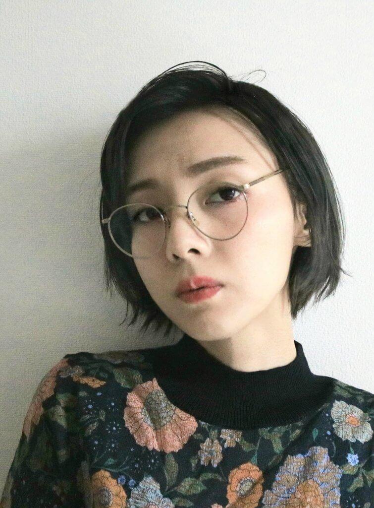 メガネをかけたブルージュカラーのショートヘアの女性の写真