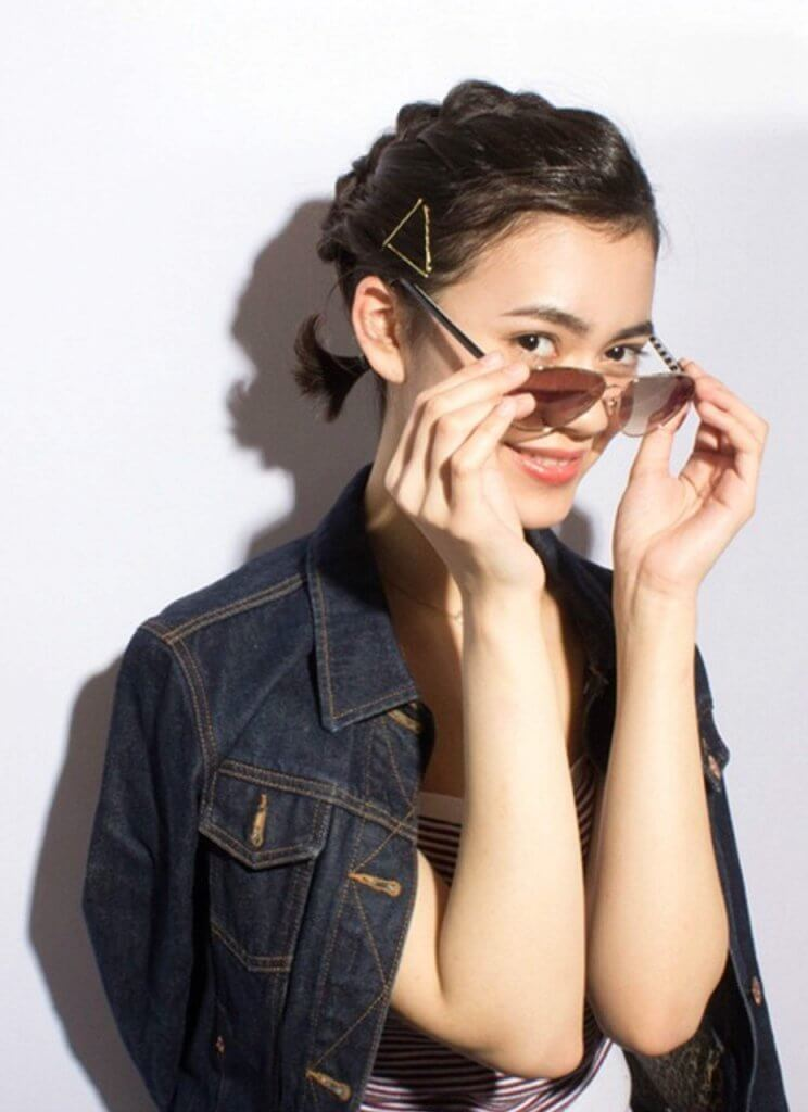 サングラスを外す、短く髪を2つに束ねた女性の写真