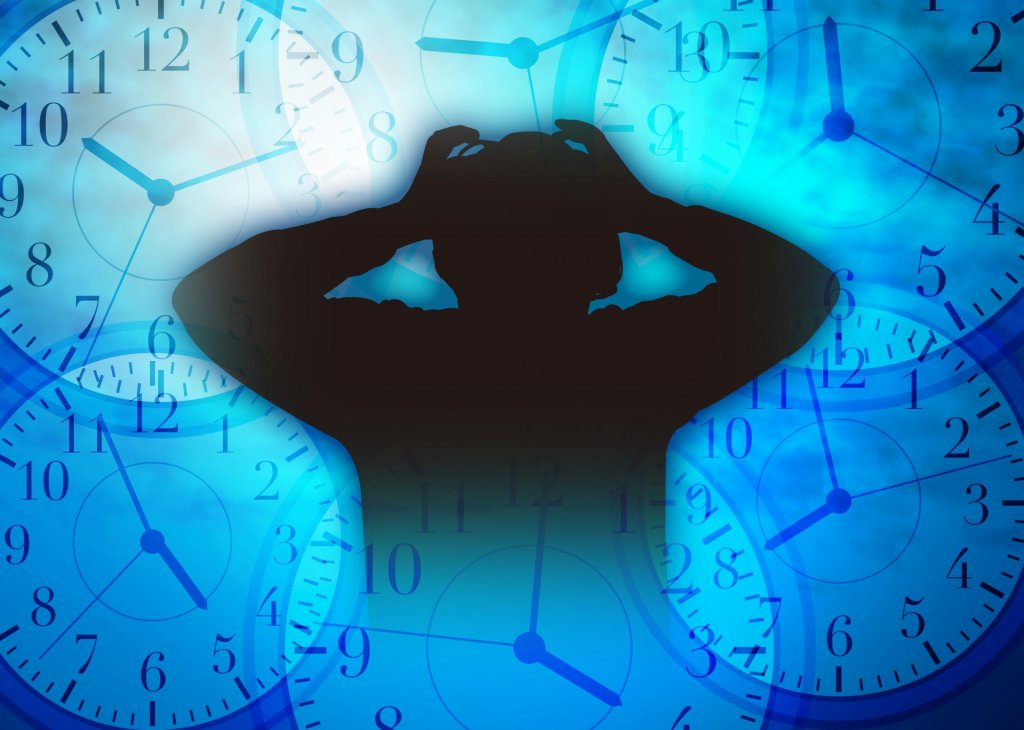 時計と頭を抱える男性の写真