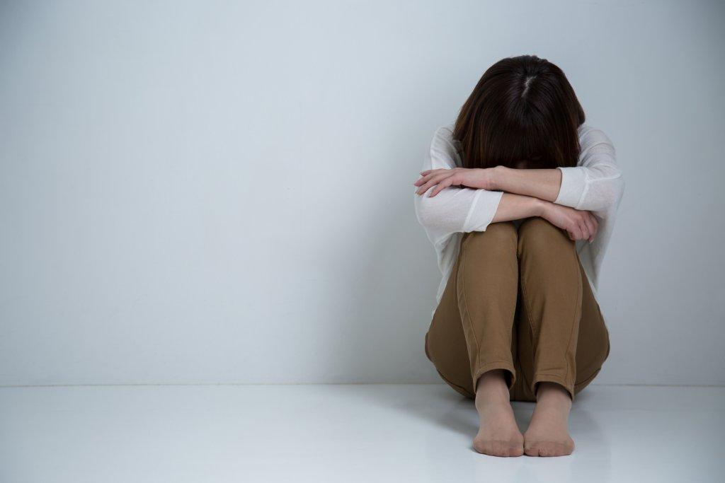 膝を抱えた女性の写真
