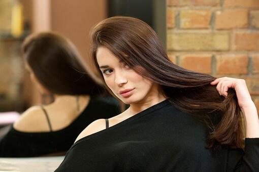 自分の綺麗な髪を触る女性の写真