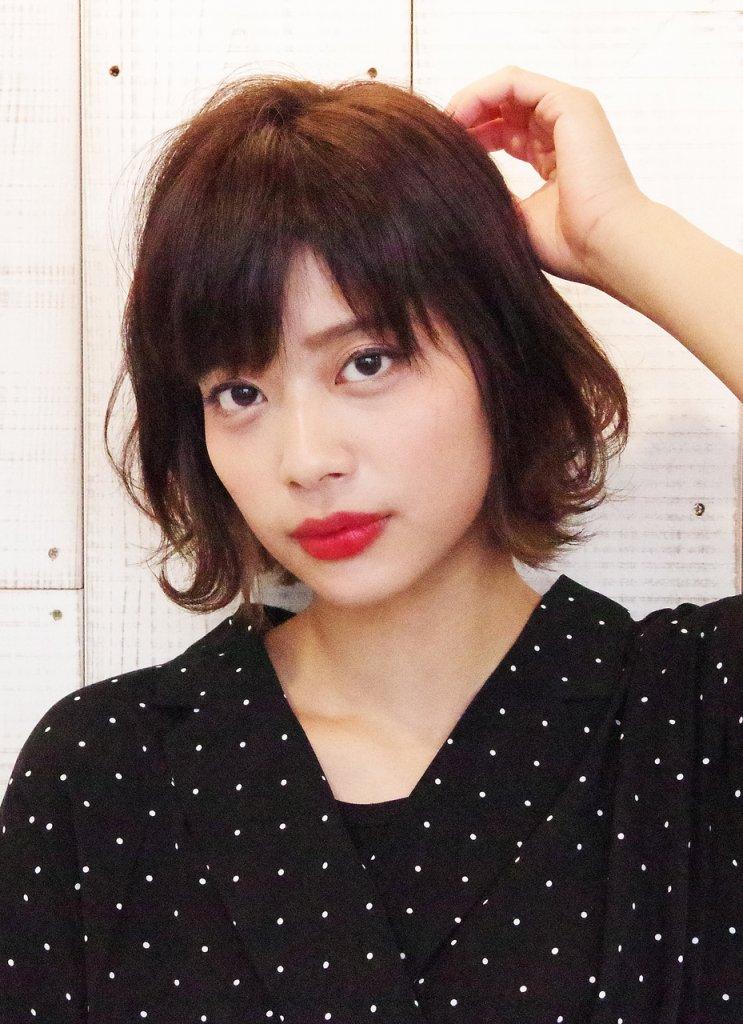 ふんわりとしたボブスタイルの髪をかきあげる女性の写真