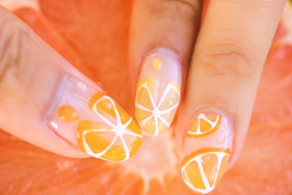 オレンジの輪切り風のジェルネイルをした指