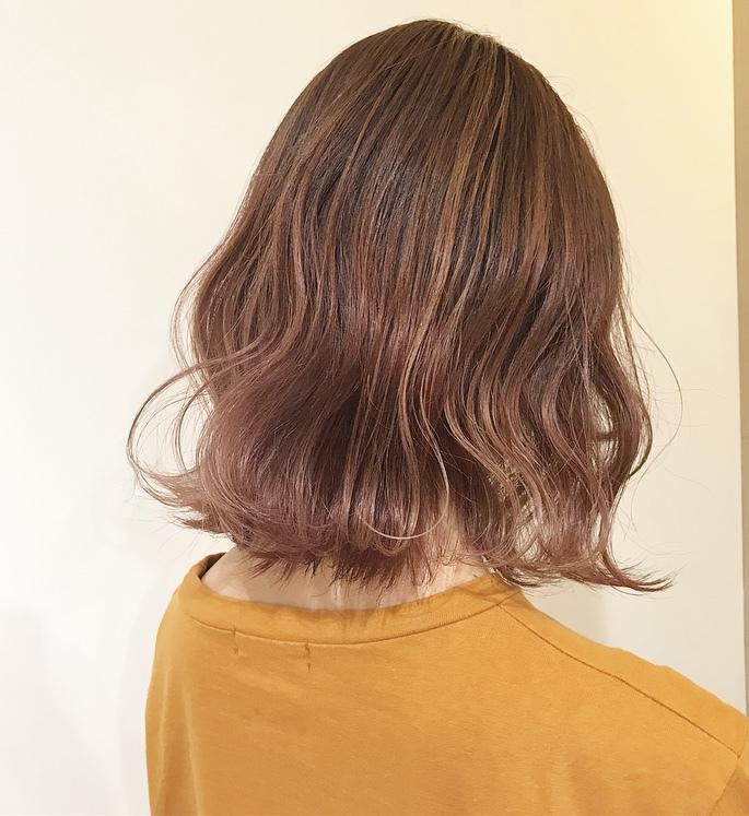 後ろを向くピンクブラウンカラーヘアの女性