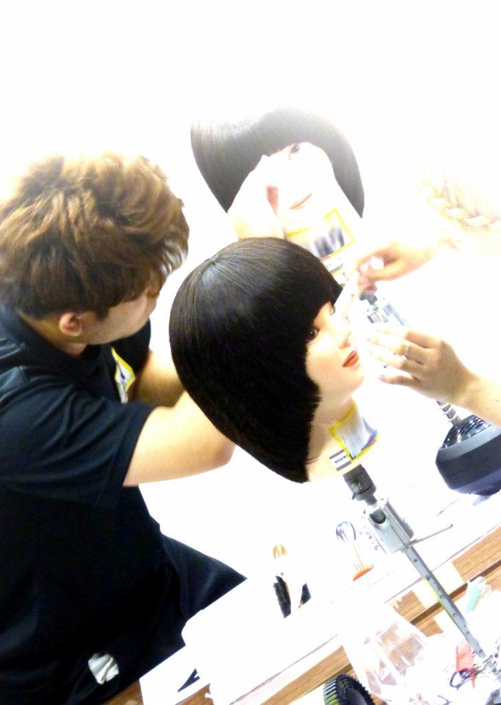マネキンをカットする美容師の写真